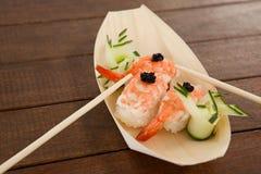 Trois sushi de nigiri ont servi avec des baguettes dans le plat en bois de bateau Images stock