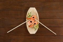 Trois sushi de nigiri ont servi avec des baguettes dans le plat en bois de bateau Photographie stock libre de droits