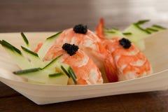 Trois sushi de nigiri servis dans le plat en bois de bateau Images stock