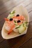 Trois sushi de nigiri servis dans le plat en bois de bateau Photos stock