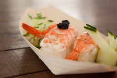 Trois sushi de nigiri servis dans le plat en bois de bateau Photo stock