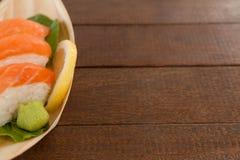 Trois sushi de nigiri servis dans le plat en bois de bateau Photos libres de droits