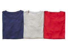 Trois T-shirts fois d'isolement Images stock