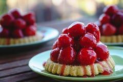 Trois tartes minuscules de fraise des plats verts photo stock