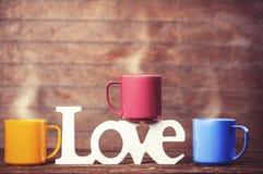 Trois tasses de café et d'amour de mot Photo stock