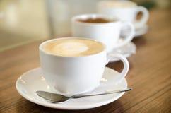 Trois tasses de coffe dans la ligne diagonale Photos stock