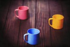 Trois tasses de couleur sur la table woodent Images libres de droits