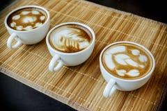 Trois tasses de latte de cafe avec trois formes d'art de latte Image libre de droits