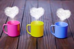 Trois tasses de thé ou de café avec des formes de coeur Images stock