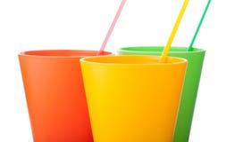 Trois tasses en plastique colorées avec des pailles d'isolement sur le blanc Photographie stock libre de droits