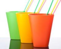 Trois tasses en plastique colorées avec des pailles sur le blanc Photo stock