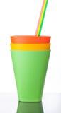 Trois tasses en plastique colorées avec des pailles sur le blanc Image stock