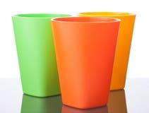 Trois tasses en plastique colorées sur le blanc Image libre de droits