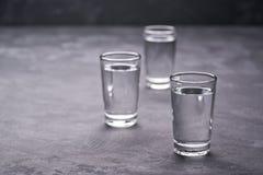 Trois tirs de vodka sur la table noire, l'espace de copie images stock