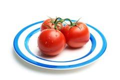Trois tomates avec des baisses de l'eau de plaque Image libre de droits