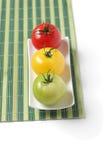 Trois tomates colorées sur le couvre-tapis en bambou Images libres de droits