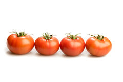Trois tomates de regard réalistes se situant dans une triangle d'isolement à l'arrière-plan blanc Images stock