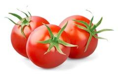Trois tomates fraîches avec les feuilles vertes d'isolement dessus photographie stock libre de droits
