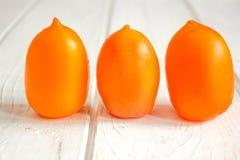 Trois tomates oranges sur le conseil en bois blanc Photographie stock