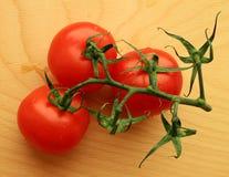 Trois tomates sur une brindille sur une planche à découper en bois images stock