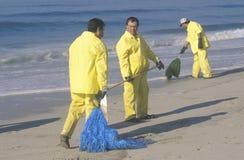 Trois travailleurs de nettoyage d'huile nettoyant la plage avec le matériel adsorbant après une flaque d'huile ont couvert le Hun Images libres de droits
