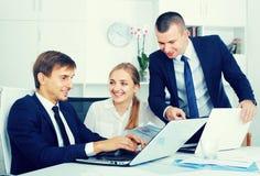 Trois travailleurs de sourire d'affaires tenant des documents photos libres de droits