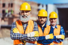 Trois travailleurs de travail posant avec des bras ont croisé au Photo stock