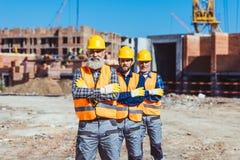Trois travailleurs de travail posant avec des bras ont croisé au Image libre de droits