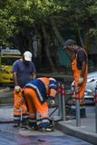Trois travailleurs ont martelé des colonnes près du trottoir image libre de droits