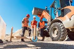 Trois travailleurs sur le chantier de construction de travaux routiers image libre de droits