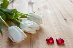 Trois tulipes blanches et deux coeurs rouges sur un fond en bois clair Images libres de droits