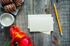 Trois tulipes colorées sur une table en bois Blanc de bloc-notes pour le texte Tasse de café, biscuits Image libre de droits