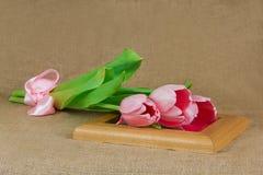 Trois tulipes roses avec le ruban de satin se trouvant sur le cadre Images stock