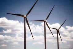 Trois turbines de vent dans l'ordre presque parfait contre un ciel bleu nuageux Images libres de droits