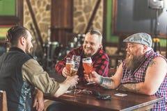 Trois types agréables appréciant la bière blonde allemande fraîche Images libres de droits