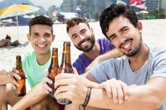 Trois types buvant de la bière à la plage Photo libre de droits