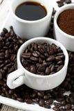 Trois types de marc de café, de grain et de boisson dans des tasses blanches Photographie stock libre de droits