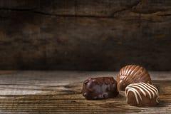 Trois types différents de bonbons au chocolat au-dessus de bois rustique Photos libres de droits
