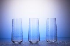 Trois verres à boire vides dans les gouttes de l'eau Photographie stock libre de droits