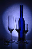 Trois verres à vin, un chandelier et une bouteille Photo stock