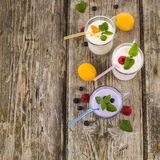 Trois verres avec les smoothies ou le yaourt avec les baies fraîches sur a Photographie stock libre de droits