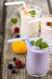 Trois verres avec les smoothies ou le yaourt avec les baies fraîches sur a Photographie stock