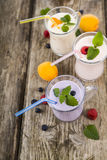 Trois verres avec les smoothies ou le yaourt avec les baies fraîches sur a Images libres de droits