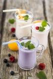 Trois verres avec les smoothies ou le yaourt avec les baies fraîches sur a Photos stock