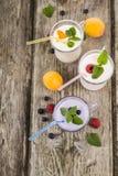 Trois verres avec les smoothies ou le yaourt avec les baies fraîches sur a Photo stock
