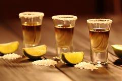 Trois verres courts avec de l'alcool à côté d'une tranche de chaux et de sel sont sur une vieille table rustique avec la texture  photo libre de droits