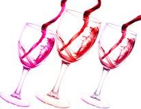 Trois verres d'éclaboussure d'abrégé sur vin rouge d'isolement sur le blanc Images stock