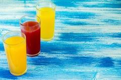 Trois verres de boissons non alcoolisées sont sur un fond bleu Boissons d'été et mode de vie sain image libre de droits