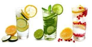 Trois verres de detox arrosent avec le fruit d'isolement sur le blanc Photo stock