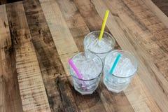 Trois verres de glace de tube avec différentes pailles de couleur sur la table en bois de courbe Images stock